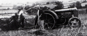 This is the second tractor on the farm with the wide, flowing mudguards. The exhaust want under the rear axle as on the later green model. Kenneth Orchard's father is working on the string box of the Massey Harris binder.
