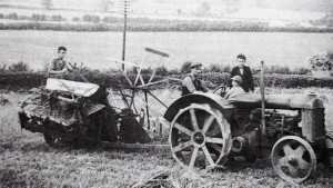 Kenneth Orchard wonders what the health and safety would make of this picture. His father is driving, Kenneth is sitting on the mudguard, his brother is sitting on the pile of sacks, and on the McCormick binder (which the string box fell off) is his cousin. This was the orange tractor, and the cleats look almost worn out, but spade lugs were fitted later.