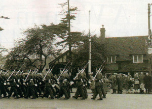 Having just received the Freedom of Entry into the borough, the parading airmen with bayonets fixed pass a cluster of British flags on their return to base. The Central Band was at the head of this procession on March 19 1960.