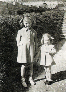 Ann (right) and her elder sister Pat with matching home-made blue coats in 1941.
